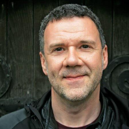 Rainer Killius, Sänger und Komponist, Portraitfotografien vor Holztür mit Beschlägen