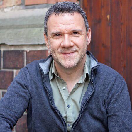 Rainer Killius, Sänger und Komponist, Portraitfoto mit Backsteinfassade, Hochformat